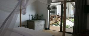 Slaapkamer met groot 2-persoonsbed en klamboe